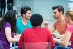 Un grupo de adolescentes que se sientan en la tabla en café, usando el ordenador portátil y el zumo de naranja de consumición Fotos de archivo libres de regalías