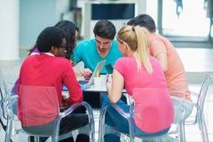 Un grupo de adolescentes que se sientan en la tabla en café, usando el ordenador portátil y el zumo de naranja de consumición Imagen de archivo libre de regalías