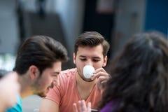 Un grupo de adolescentes que se sientan en la tabla en café, usando el ordenador portátil y el zumo de naranja de consumición Imágenes de archivo libres de regalías