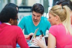Un grupo de adolescentes que se sientan en la tabla en café, usando el ordenador portátil y el zumo de naranja de consumición Imagenes de archivo