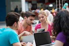 Un grupo de adolescentes que se sientan en la tabla en café, usando el ordenador portátil y el zumo de naranja de consumición Fotos de archivo