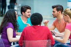 Un grupo de adolescentes que se sientan en la tabla en café, usando el ordenador portátil y el zumo de naranja de consumición Fotografía de archivo libre de regalías