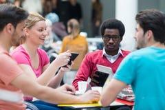 Un grupo de adolescentes que se sientan en la tabla en café, usando el ordenador portátil y el zumo de naranja de consumición Foto de archivo libre de regalías