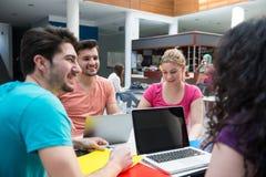 Un grupo de adolescentes que se sientan en la tabla en café, usando el ordenador portátil y el zumo de naranja de consumición Foto de archivo