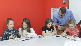 Un grupo de alumnos examina la preparación para la lección almacen de video