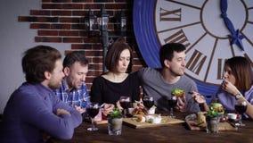 Un grupo de amigos adultos que no se han visto comer la cena en un restaurante, hablando de la comida trajeron almacen de metraje de vídeo