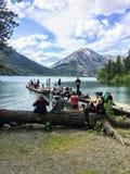 Un grupo de amigos del caminante que cuelgan hacia fuera por las orillas del lago Waterton foto de archivo
