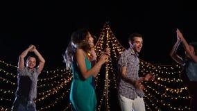 Un grupo de amigos está bailando en etapa, son activamente de salto y cantantes almacen de video