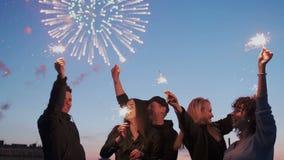 Un grupo de amigos jovenes bonitos y atractivos que se colocan en el tejado de la ciudad y que gozan del fuego artificial enorme  almacen de video