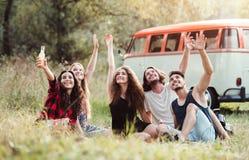 Un grupo de amigos jovenes con las bebidas que se sientan en hierba en un roadtrip a través de campo imagen de archivo