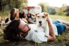 Un grupo de amigos jovenes con un perro que se sienta en hierba en un roadtrip a través de campo imágenes de archivo libres de regalías