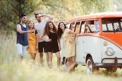 Un grupo de amigos jovenes en un roadtrip a través del campo fotografía de archivo libre de regalías