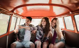 Un grupo de amigos jovenes en un roadtrip a través del campo, sentándose en un minivan foto de archivo libre de regalías