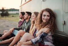 Un grupo de amigos jovenes en un roadtrip a trav?s del campo, sent?ndose por un minivan foto de archivo libre de regalías