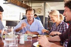 Un grupo de amigos que almuerzan en un restaurante Imagenes de archivo