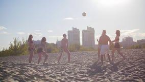 Un grupo de amigos que juegan a voleibol en la playa contra una puesta del sol hermosa fotografía de archivo