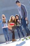 Un grupo de amigos que se divierten con el patín en la calle Fotografía de archivo