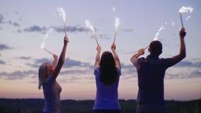 Un grupo de amigos que se divierten con los fuegos artificiales o las luces de Bengala vídeo de la cámara lenta