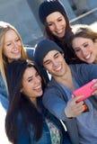 Un grupo de amigos que toman las fotos con un smartphone Fotos de archivo