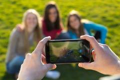 Un grupo de amigos que toman las fotos con un smartphone Imagen de archivo libre de regalías