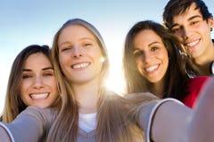 Un grupo de amigos que toman las fotos con un smartphone Imagen de archivo