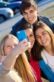 Un grupo de amigos que toman las fotos con un smartphone Fotos de archivo libres de regalías