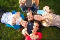 Un grupo de amigos que toman las fotos con un smartphone Foto de archivo libre de regalías