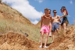 Un grupo de amigos de risa se coloca en un campo, muchachas hermosas y muchachos en vacaciones en un fondo borroso natural Fotografía de archivo