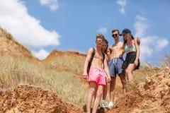 Un grupo de amigos de risa se coloca en un campo, muchachas hermosas y muchachos en vacaciones en un fondo borroso natural Imágenes de archivo libres de regalías