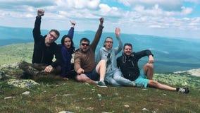 Un grupo de amigos, turistas que descansan encima de la montaña metrajes