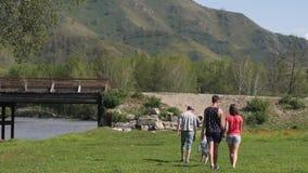 Un grupo de amigos y un niño de vacaciones están caminando en las montañas el hijo camina con su padre y una compañía de almacen de video