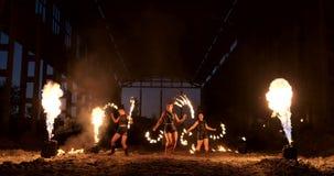 Un grupo de artistas profesionales con el fuego muestra la demostración que hacen juegos malabares y que bailan con el fuego en l almacen de metraje de vídeo