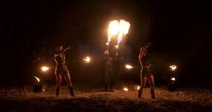 Un grupo de artistas profesionales con el fuego muestra la demostración que hacen juegos malabares y que bailan con el fuego en l almacen de video