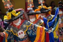 Un grupo de bailarines enmascarados en el traje tradicional de Ladakhi que realiza la danza de Chaam en el festival anual de Hemi foto de archivo