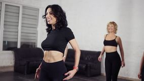 Un grupo de bailarines de sexo femenino atractivos en los movimientos básicos practicantes del bachata del salón de baile Mujeres metrajes