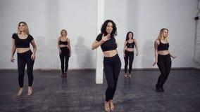 Un grupo de bailarines de sexo femenino del bachata que recolectan en el centro de salón de baile para aprender y para bailar los metrajes