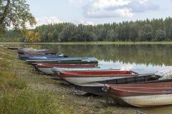 Un grupo de barcos en la playa por el lago en el otoño Fotos de archivo libres de regalías