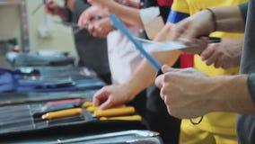 Un grupo de cocineros afila los cuchillos Las cocinas se preparan para la clase principal almacen de metraje de vídeo