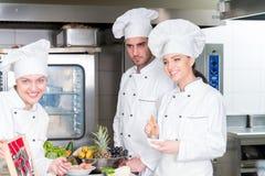 Un grupo de cocineros jovenes prepairing la comida en restaurante de lujo imagen de archivo libre de regalías