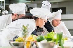 Un grupo de cocineros jovenes prepairing la comida en restaurante de lujo foto de archivo
