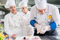 Un grupo de cocineros jovenes prepairing la comida en restaurante de lujo foto de archivo libre de regalías