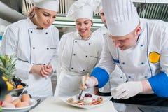 Un grupo de cocineros jovenes prepairing la comida en restaurante de lujo fotografía de archivo