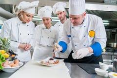 Un grupo de cocineros jovenes prepairing la comida en restaurante de lujo imagenes de archivo