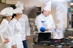 Un grupo de cocineros que preparan la comida deliciosa en alto restaurante de lujo imagen de archivo libre de regalías