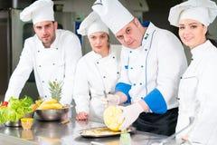 Un grupo de cocineros que preparan la comida deliciosa en alto restaurante de lujo fotografía de archivo