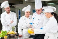 Un grupo de cocineros que preparan la comida deliciosa en alto restaurante de lujo fotos de archivo libres de regalías