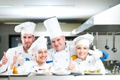Un grupo de cocineros que presentan con la comida deliciosa en alto restaurante de lujo imagenes de archivo