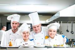 Un grupo de cocineros que presentan con la comida deliciosa en alto restaurante de lujo fotografía de archivo libre de regalías