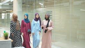 Un grupo de cuatro muchachas multiétnicas musulmanes jovenes que charlan y que caminan junto en centro de negocio metrajes