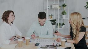 Un grupo de diseñadores enfocados jovenes de arquitectos está discutiendo el plan de un complejo residencial de varios pisos mo metrajes